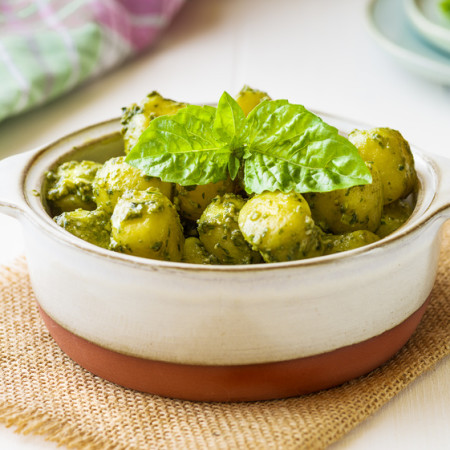 Gnocchi with 'Pesto' sauce, in terracotta bowl, on wooden background.