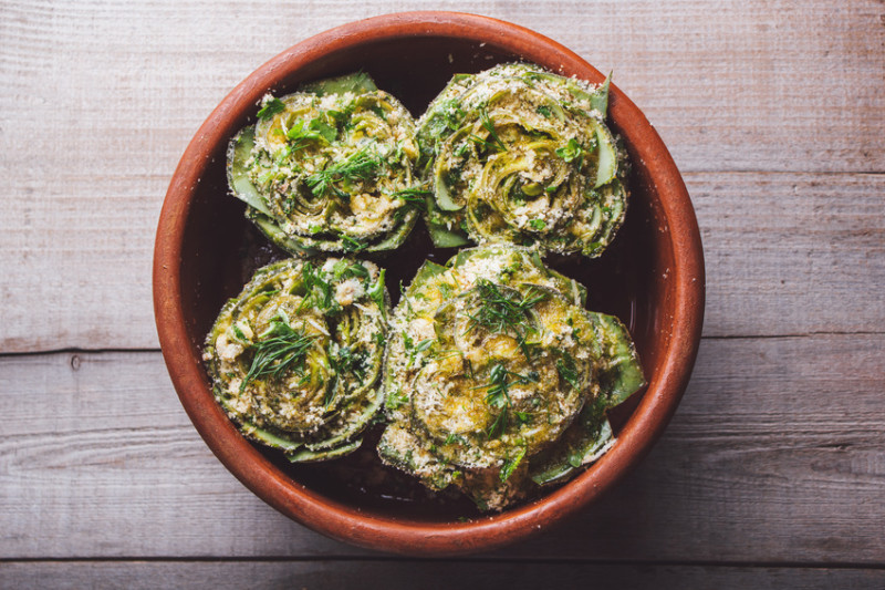 Cooked artichokes with parsley and parmesan, served in a clay dish on a wooden table